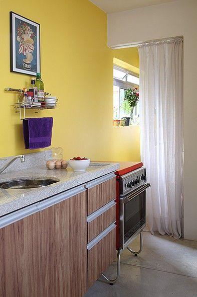 Ainda no projeto do escritório Arquitetura Paralela, para economizar espaço na cozinha, a porta para a lavanderia foi substituída por uma cortina de gaze de linho. O fogão antigo em bom estado foi herança da avó da moradora
