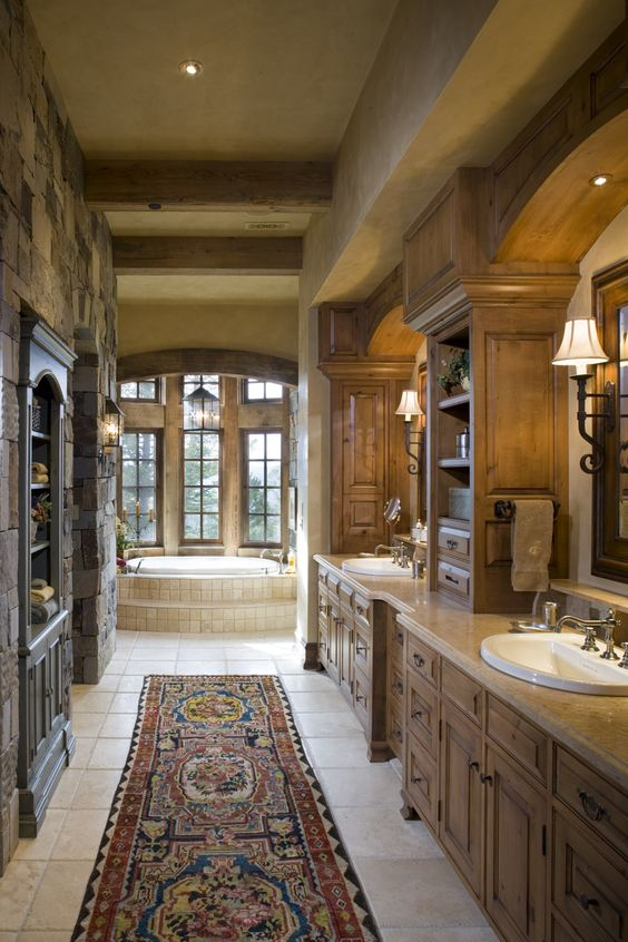 Master bath.  Stone wall.  Wood Beam ceiling. Wall-mounted sconces on mirrors.  Designed by Locati Interiors.