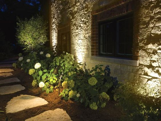 """22 Landscape Lighting Ideas: This exterior is also uplit to highlight the stonework, and a path light in front spreads its beam over a bank of hydrangeas. """"Hydrangeas love landscape lighting,"""" says Dross of Kichler Lighting. """"They should be stage actors."""" They reflect light dramatically when they're in flower, but they also create dancing shadows in winter because they retain their faded leaves and blooms. It's smart to think about what any..."""