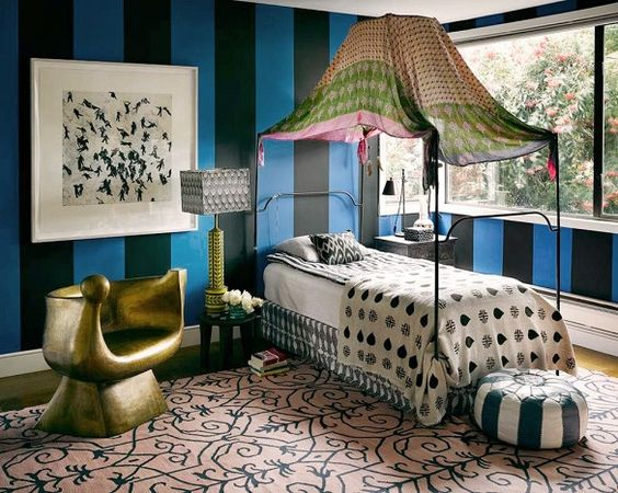 Eclectic and graphic bedroom with striped walls, patterned wallpaper, and canopy twin bed.