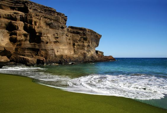 The extraordinary olive-green sands of Papakolea Beach are located near the southern tip of Hawaii's Big Island. The sand comes from small green volcanic stones that originated from the lava cliffs surrounding the small bay