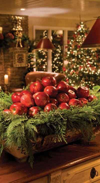 Holiday greenery mixed with bright red apples makes a beautiful and inexpensive display....: