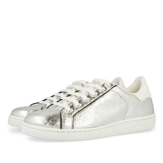 Sneaker de mujer en color plata brillante. Detalles y cordones en blanco. Corte…