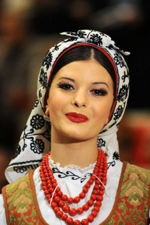 Un cantante popular polaca lleva una cubierta de la cabeza con bordados típicos de la ciudad de Hrubieszów en Este de Polonia.  Ella también lleva los granos rojos tradicionales que se encuentran en muchos trajes típicos durante todo Polonia y el resto del mundo eslavo.  El rojo era el color asociado con la belleza y la elegancia de los antiguos eslavos.  Incluso en los tiempos modernos la palabra rusa para bella sea homónima con la palabra para el rojo.