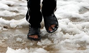 A Syrian boy walks through the Bekaa Valley refugee camp in Lebanon after a heavy snowstorm, 3 January 2016