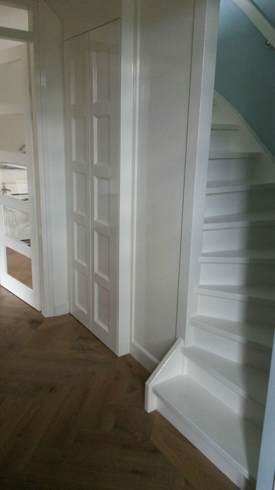 Hal met trapkast, paneeldeuren en dichte trap naar eerste verdieping. Eiken visgraat vloer. Alles in hoogglans wit geschilderd voor klassiek effect.