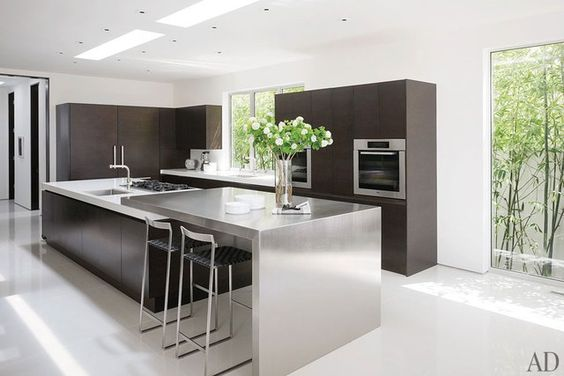 The sleek kitchen, composed of oak and stainless steel, represents a collaboration between Magni and Haefele Design. The barstools are by Mark Albrecht Studio, and the ovens are by Miele.