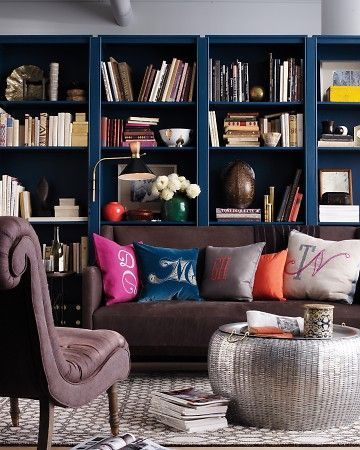 dark teal or navy bookcases, pops of hot pink and orange, metallic accents