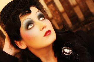 pelle diafana, matita nera intorno agli occhi, ombretti neri e grigi, sopracciglia sottili e labbra rosse dipinte a cuoricino