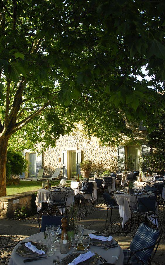 La Bastide de Marie. Gravel terrace. Big trees. Lawn. Stone. Shutters. Sunlight. Wrought iron furniture.