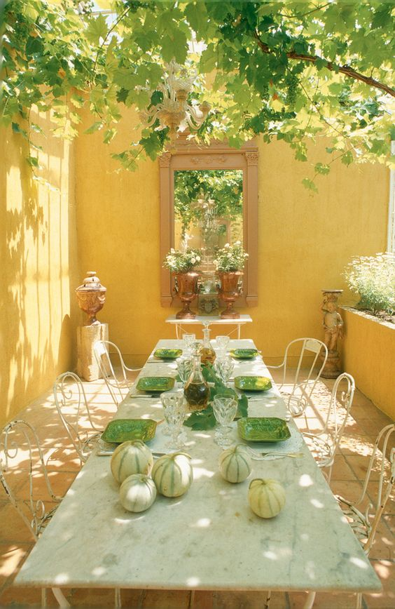 Romantic dining area with golden sunshine stucco walls in a courtyard. #provence #frenchcountry #dining #courtyard #garden #yellow