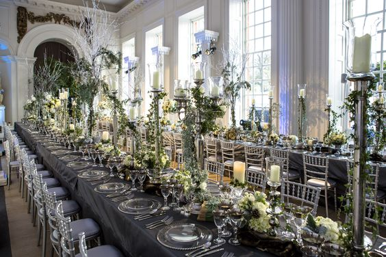 Use of tall, elegant candle sticks helps to provide extra height to the table décor in a room with very high ceilings