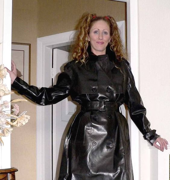 Lucinda  buckled and belted into a wonderful Shiny Black Rubber Mac.