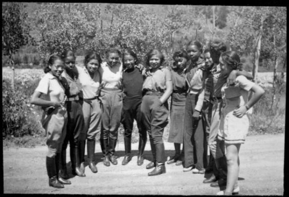 A group of African American teenage campers from Camp Nizhoni in Lincoln Hills (Gilpin County), Colorado pose. Outfits include jodhpurs with...