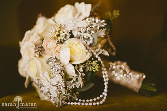 Vintage wedding bouquet -- a glamorous combination of draped pearls, sparkling brooches, pearl flowers, sola flowers, velvet leaves, fresh roses, dusty miller, and seeded eucalyptus
