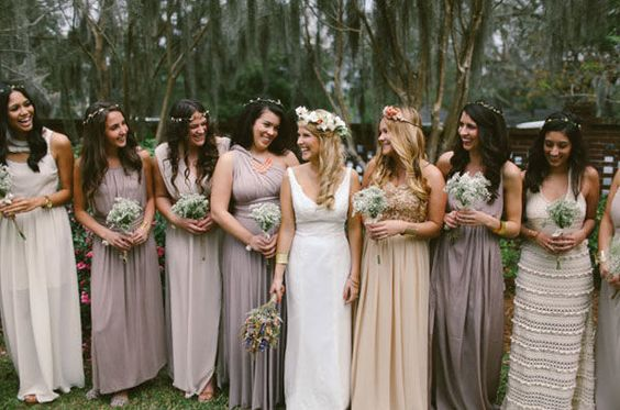 boho bridal party in mismatched, creamy neutral bridesmaid dresses holding baby's breath bouquets: