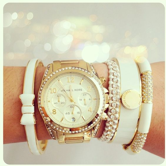 Arm Candy Inspiration: This bracelet stack is layered (from left with right) with a cream/gold Kate Spade 'Take a Bow' bracelet, a gold Michael Kors watch, a white friendship bracelet with rhinestone detail, a white/gold Henri Bendel '1985 Narrow Hinged Enamel Bangle,' and an unknown white/gold bangle with rhinestone detail.