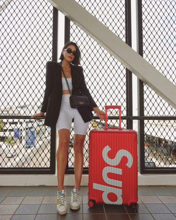 White crop top+white bike-shorts+white sneakers+black blazer+black chain bag+black sunglasses+gold pendant necklaces+red suitcase. Late Summer Travel Outfit 2018
