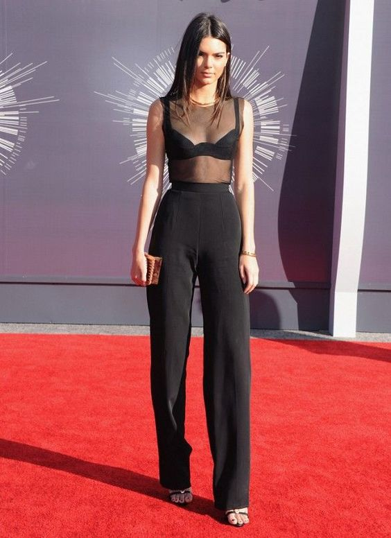 Kendall Jenner wears a sheer top, high-waisted black pants, sandals, and gold jewelry