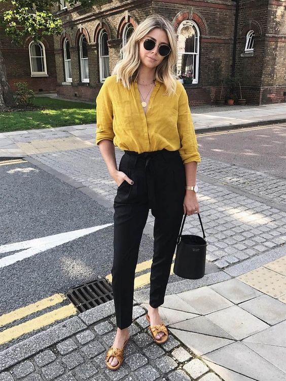 Camisa amarela com calça escura e acessórios minimalistas dourados. Elegante e minimalista.