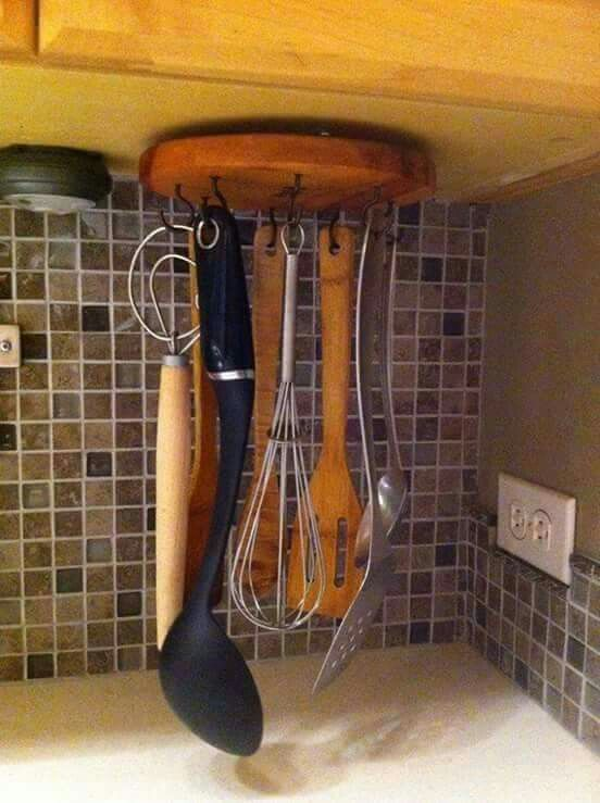 Attach a lazy Susan upside down under a cabinet and add screw hooks to hold kitchen utensils.
