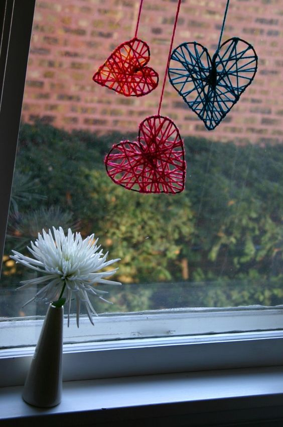 Yarn Hearts - Hearts made from rustic floral wire are wrapped with yarn and hung in the window for Valentine's Day - You could make pretty much any shapes - stars for Christmas?