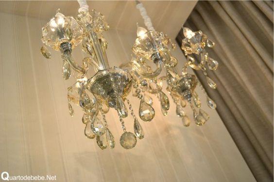 Luminária de teto de cristal com lâmpadas imitando velas.