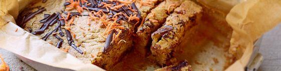 Backofen auf 200° C Ober-/ Unterhitze vorheizen., Quinoa mit 200 ml Wasser aufkochen, auf kleiner Flamme ca. 15 Min bei geschlossenem Deckel köcheln. Abkühlen lassen. , Möhren schälen und raspeln. Schokolade grob hacken. Mehl, Öl, Agavendicksaft, Quinoa-Reisdrink und Backpulver verrühren. Möhre, Schokolade und die Quinoa zügig unterrühren., Teig auf ein tiefes Blech mit Backpapier verteilen, ca. 30 Min backen.