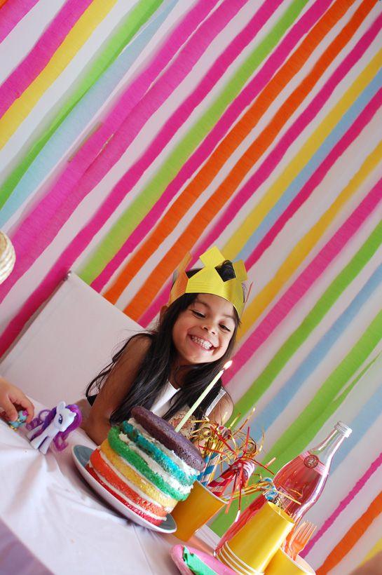 """Idea: crea un ambiente festivo en una fiesta infantil con poco trabajo colgando trozos largos de guirnaldas de cinta crepé en una pared para formar una """"cortina"""" de color"""