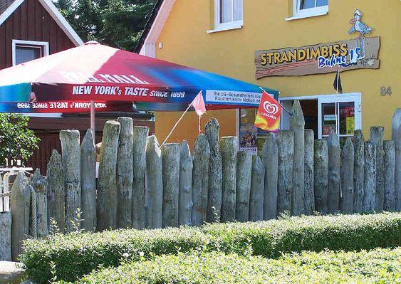 Sichtschutz-Palisadenzaun aus Holz an einem Strandimbiss an der Ostsee.
