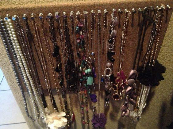 1. Buy a cheap cork board for 6-7 dlls at target or Walmart. 2. Turn it sideway 3. Place pins across the top very close together 4. Hang your necklaces!  I attached the cork board to the wall with some thumbtacks. It's pretty simple and you keep your necklaces from getting tangled!