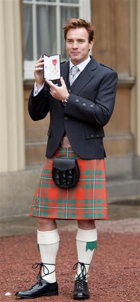 A kilted Ewan McGregor holds his OBE for services to Drama and Charity after a ceremony at Buckingham Palace in London on June 28, 2013.: