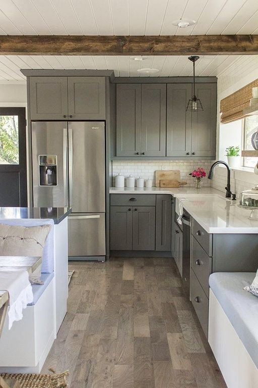 The gray cabinets here work well with the wood plank style of the floors. The L shape is offset here, with a shorter edge with the fridge and a longer one on the other side.
