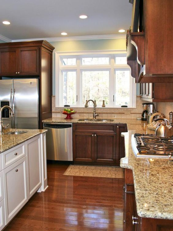 Kitchen cabinetry doesn't have to match. A creamy white island is ...