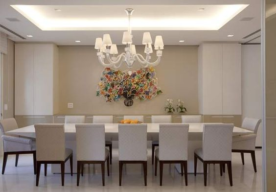 O lustre, na sala de jantar, tem a função de iluminação principal. O ideal é que a distância seja de 0,70 a 1 m de distância entre o tampo da mesa de jantar e a luminária para que a peça não obstrua o campo visual e a luz não cause desconforto. <br><br>O tamanho do lustre deve ser proporcional à mesa. Mesas maiores requerem peças mais volumosas.