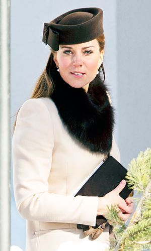 Kate Middleton, Duchess of Cambridge, in ivory coat and black fur stole. #winterfashion #winterstyle #katemiddleton