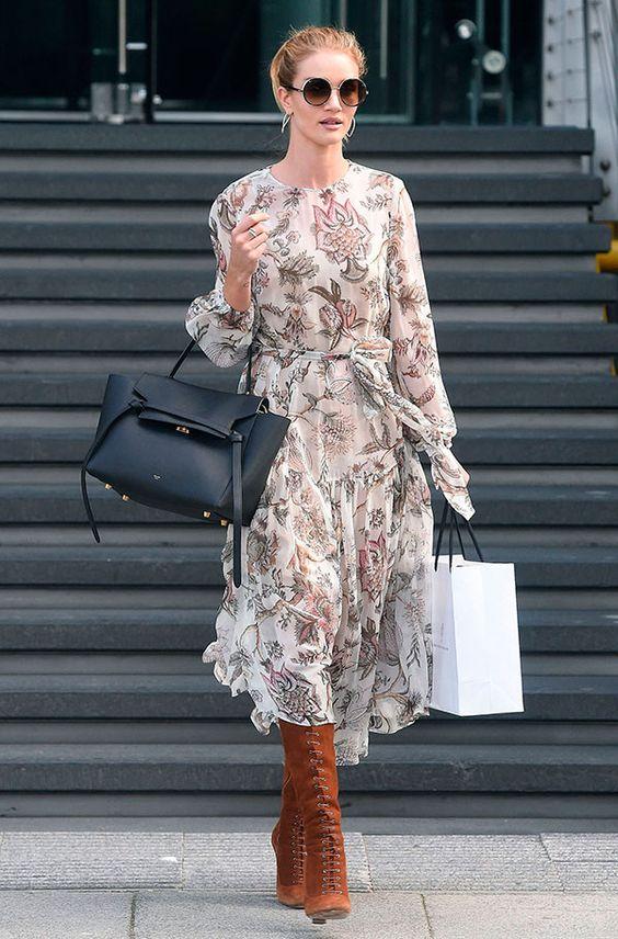 Rosie Huntington-Whiteley em street style look usando vestido longo florido, bota marrom cano alto e bolsa preta.