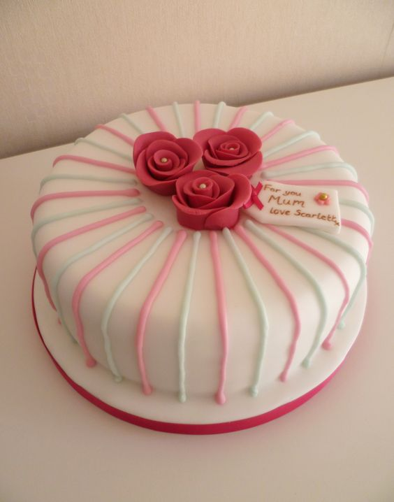 Elegant Mothers Day cake with pink sugarpaste roses and personalised tag