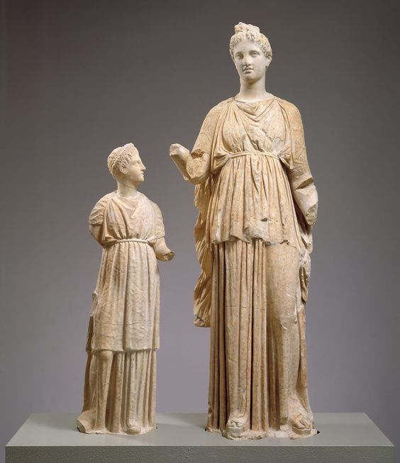 """Marble funerary statues of a maiden and a little girl. (Credit: Rogers Fund, 1994). From site: """"This distinctive manner of dress was apparently reserved for young virgins who had the honor of leading processions to sacrifice, carrying in a basket such implements as barley, fillets, and the sacrificial knife."""""""