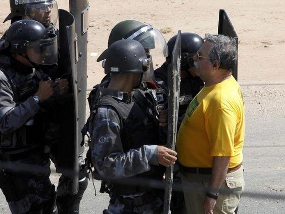 Homem fica parado enquanto policiais se aproximam para conter manifestantes (Foto: Paulo Whitaker/Reuters)