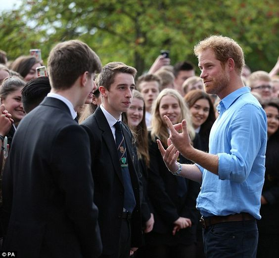Prince Harry gestures with his hands as he engages in an animated chat with…