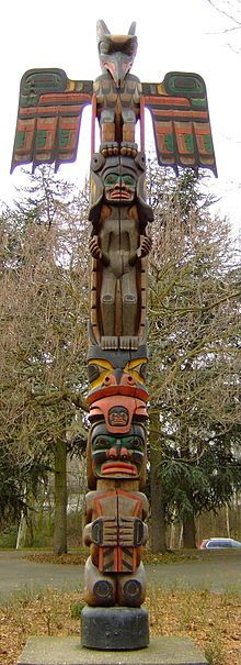 totem pole of chief Tony Hunt Kwakiutl ... top to bottom: the raven animal emblem of the Hunt family, Sisutl the serpent with two heads & character raising his hands in welcome, with head object shield-shaped