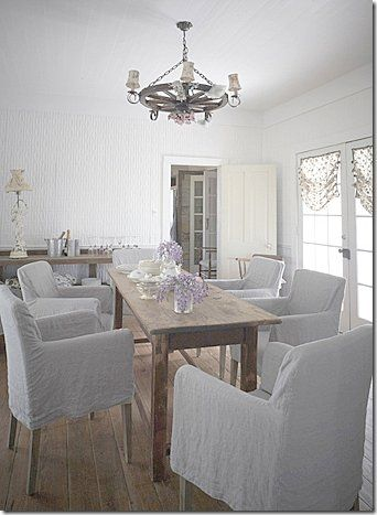 A beautiful spare shabby chic dining area with linen slipcovered dining chairs and a narrow farm table at The Prairie by Rachel Ashwell. #theprairie #shabbychic #RachelAshwell