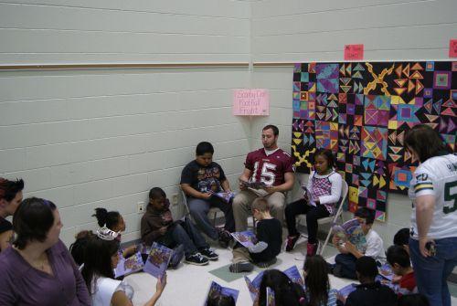 Veteran Racine Raiders quarterback Chris Walsh reads to students at Julian Thomas Elementary School.