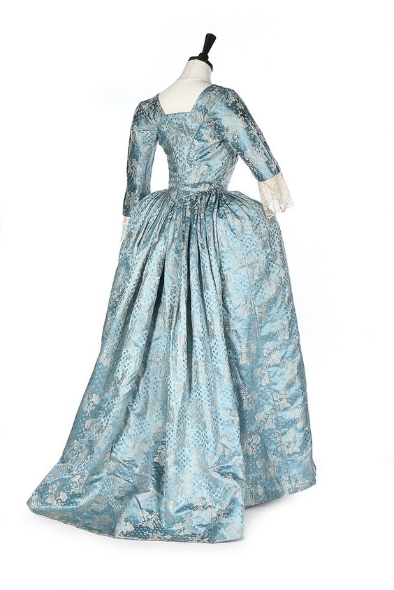 Rear view, obe à l'Anlgaise, 1760s, 19th century alterations. Tourquoise-blue silk satin, woven with mentoring white blossom, the ground figured with leaf sprigs.