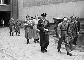 Karl Dönitz (centre, in long, dark coat) is followed by Speer (bareheaded) and Jodl (to the left of Speer) during the arrest of the Flensburg government