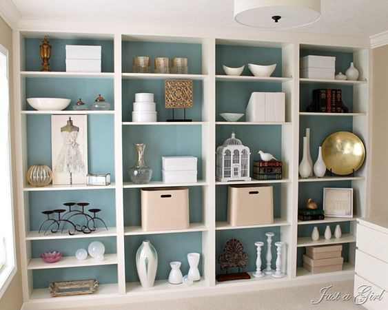 Adding color to a simple bookcase adds such 'wowfactor'.  You can do it inexpensively without the mess of paint by using fabric attached with spray adhesive to foam core board cut to fit inside the bookcases.  Then just replace the shelves. Easily changed when you change your decor.