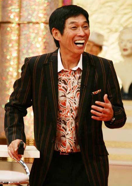 ストライプのジャケットを着て立っている明石家さんまの画像・壁紙