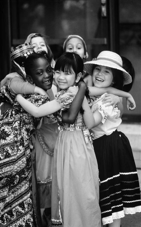 © UNICEF/Shelley Rotner - A group of girls dressed in their national costumes embrace at the United Nations in New York City. 1979. S)