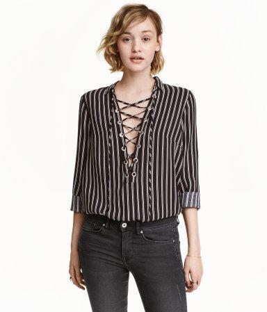 Schwarz/Weiß gestreift. Bluse aus weichem Viskosestoff. Die Bluse hat einen V-Ausschnitt mit Kragen und Schnürung sowie einen abgerundeten Saum.